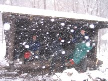 Snow accumulating very fast in front of the lean-to while the group eats lunch huddled inside.